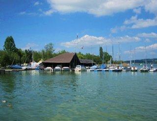 Aus diesem Blickwinkel sehen Sie das Bootshaus der Segel- und Surfschule Mattsee von der Seepromenade aus © Steiner Nautic